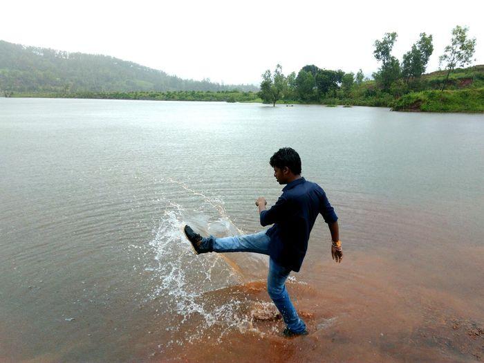 Full length of man kicking water at lakeshore
