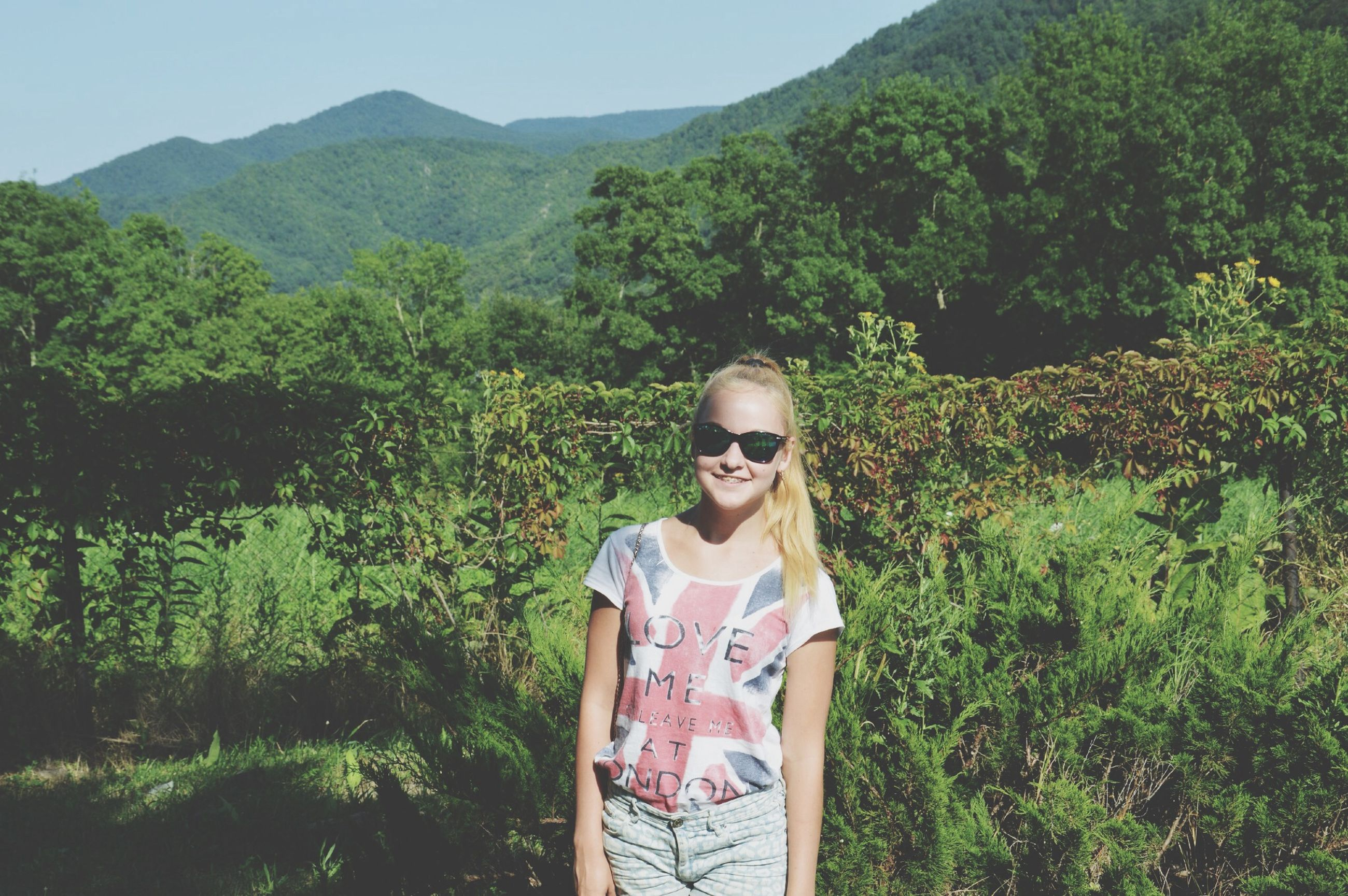 mountain, casual clothing, lifestyles, person, leisure activity, tree, standing, young adult, three quarter length, waist up, green color, nature, growth, beauty in nature, tranquility, smiling, portrait, looking at camera