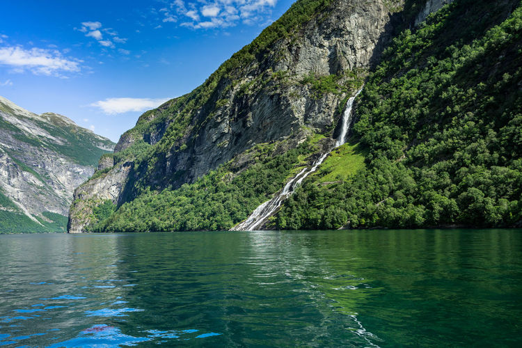 Landscape of Geirangerfjord with the Friar (or the Suitor) waterfall, Sunnmore, More og Romsdal, Norway Norway Norway🇳🇴 Norge Norwegian Scandinavia Northern Europe Fjord Geirangerfjord Geiranger Geiranger Fjord UNESCO World Heritage Site Unesco Water Mountain Beauty In Nature Scenics - Nature Tranquility Sky Tranquil Scene Nature Day Waterfront Tree No People Non-urban Scene Mountain Range Plant Lake Idyllic Outdoors Remote Formation