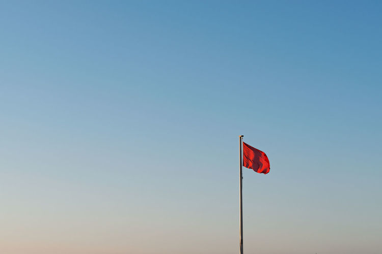 Red Flag at the Beach Ocean Fine Art Coast Photography Salt Water Coastline Fine Art Photography Fine Art Fineart Empty Space negative space Blue Print Poster Red Clear Sky Patriotism Flag Blue Sky Golf Course Golf