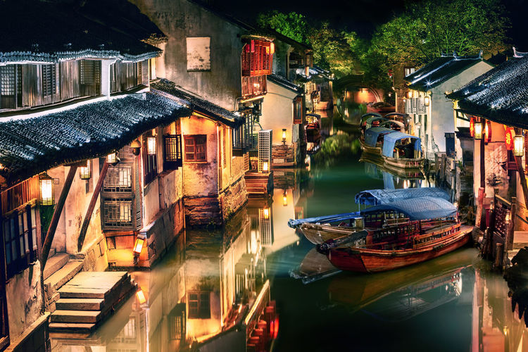Boats moored in canal amidst buildings in city at night