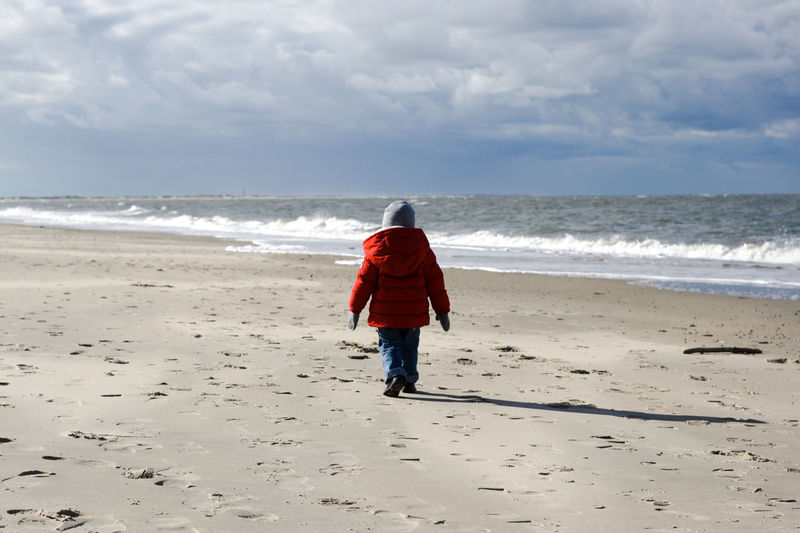 Land Beach Rear View Sea Full Length Sky Water One Person Nature Cloud - Sky Real People Sand Motion Casual Clothing Horizon Over Water Walking Horizon Day Outdoors Warm Clothing Autumn Fall Wind Hat Red Red Color Child Childhood Northsea Gloves Jeans Dramatic Sky October