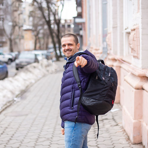 Smiling man poiting in camera and smiling while walking on the street of city Architecture One Person Winter Looking At Camera Real People City Clothing Warm Clothing Three Quarter Length Focus On Foreground Standing Young Adult Lifestyles Portrait Building Exterior Built Structure Front View Street Jacket Scarf Outdoors Urban City Walking