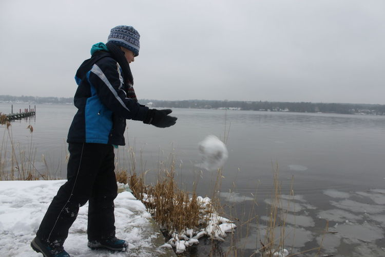 Teenage boy wearing warm clothing while standing by lake during winter
