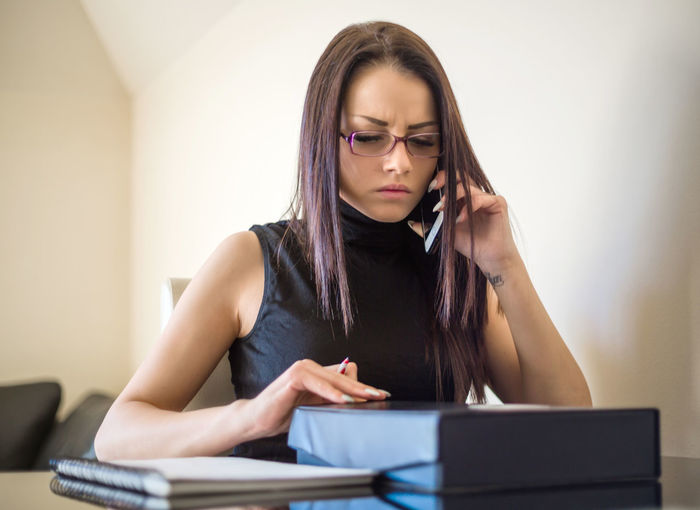 Businesswoman Using Phone While Sitting At Table In Office