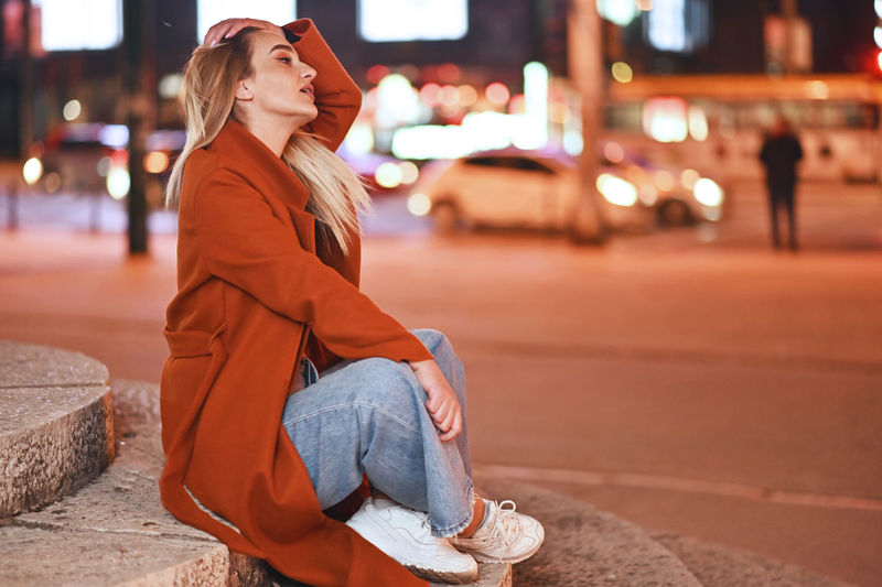 Young woman looking away while sitting on street in city at night