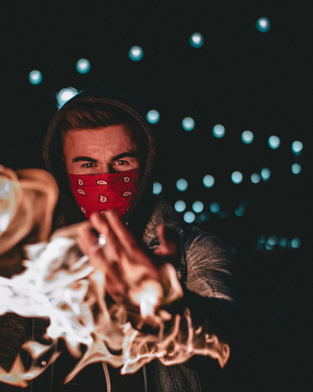 Portrait Of Young Man Wearing Mask By Fire In Night