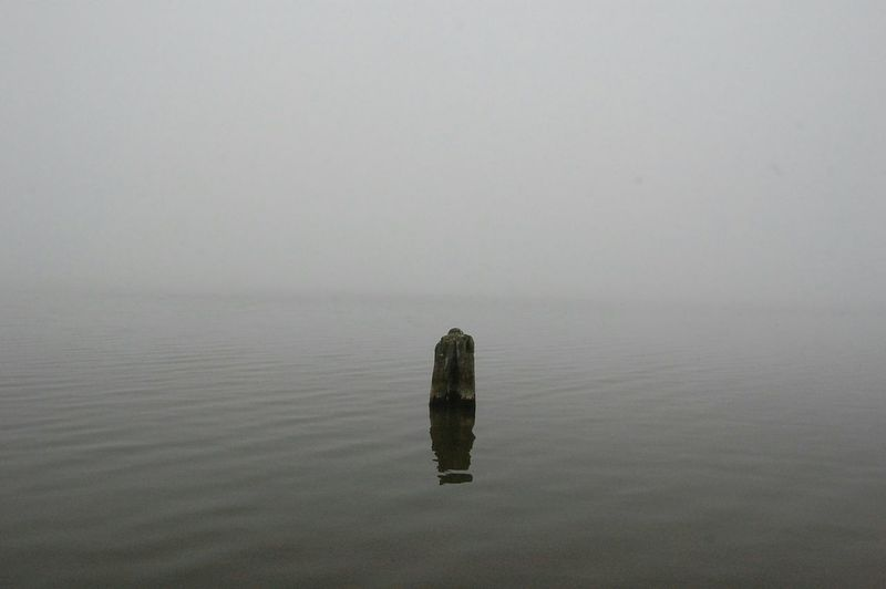 View of wooden post in calm sea