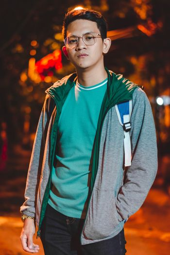 Portrait Of Young Man Standing On Footpath At Night