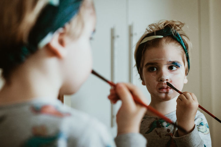 Close-up of girl painting her face in home
