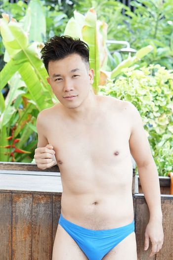 Portrait of shirtless man standing against plants