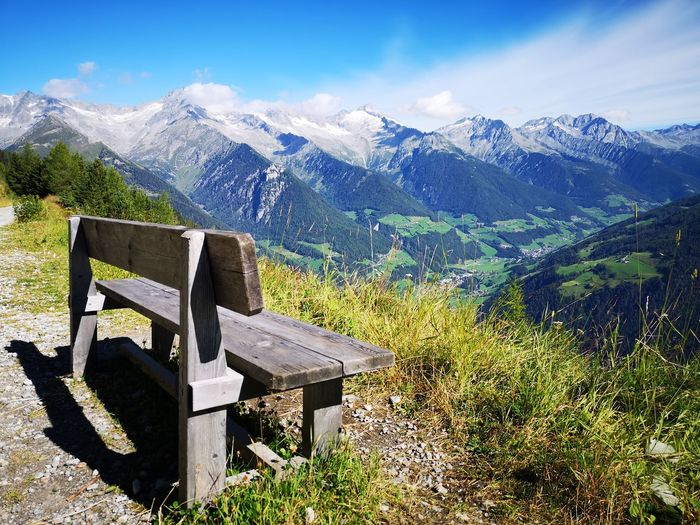Bench by snowcapped mountains against sky