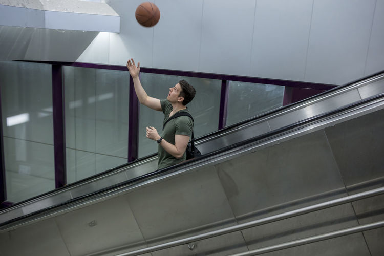 A man riding an escalator with a basketball in hand. 1 Person Adult Afternoon Athletic Basketball Descending Long Shot Man Profile Tossing Ball Caucasian Day Escalator Handsome Interior Male Playing Rail Riding Sportswear Sporty T-shirt Throwing  White