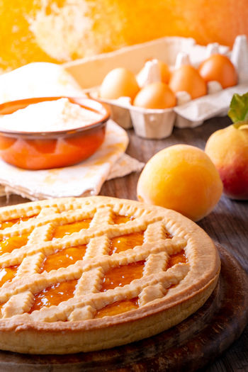 Tart with peach jam on wooden rustic table Tart Apricot Baked Pastry Item Bread Breakfast Cheese Choice Close-up Dairy Product Food Food And Drink Freshness Fruit Healthy Eating Meal No People Orange Orange Color Peaches Pie Selective Focus SLICE Snack Sweet Food Variation