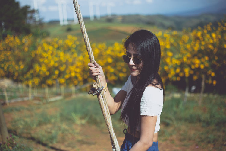 Woman holding rope while standing against flowering plants