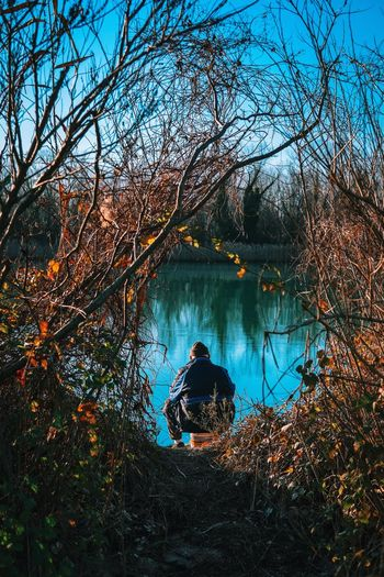 Man sitting by lake in forest