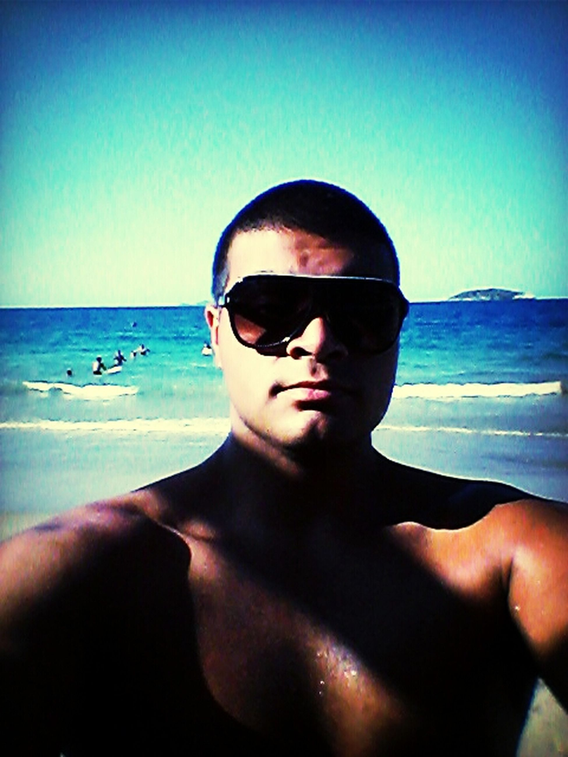 sea, water, horizon over water, beach, lifestyles, clear sky, leisure activity, copy space, young adult, sky, headshot, shore, person, sunglasses, blue, vacations, young men, holding