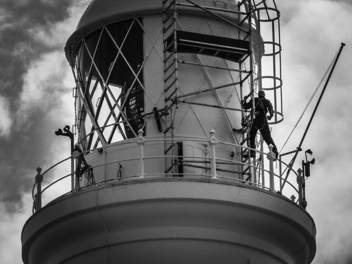 Men At Work  Black And White Painting. Bracing Fresh Windy Day Sky Lighthouse Guidance Direction