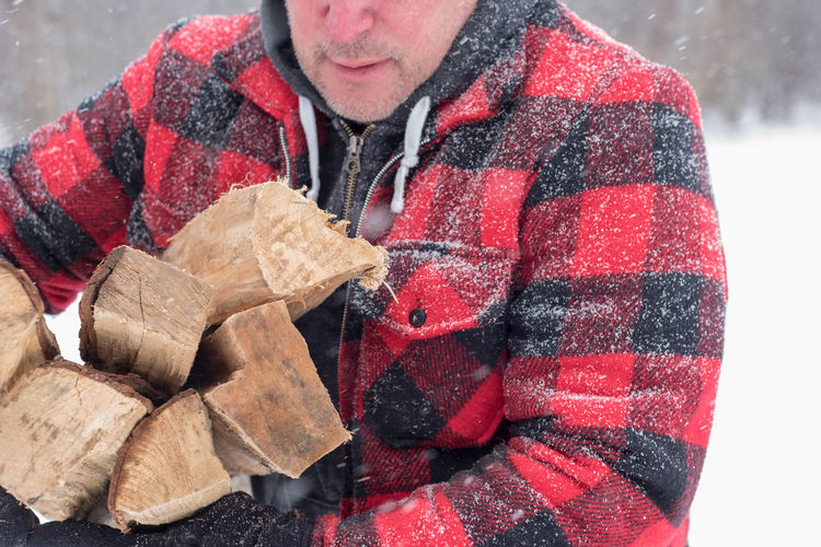 Midsection Of Mature Man With Wood Standing Outdoors During Snow Fall