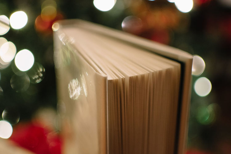 Close-up of book against illuminated lights