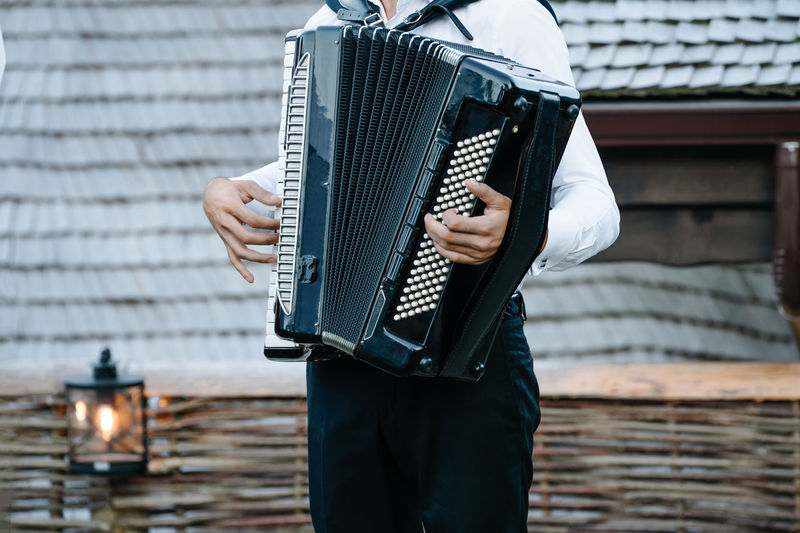 Midsection of man playing accordion while standing outdoors