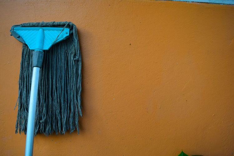 Blue Mop On Brown Wall