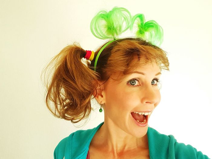 Portrait of cheerful woman wearing headband against white background