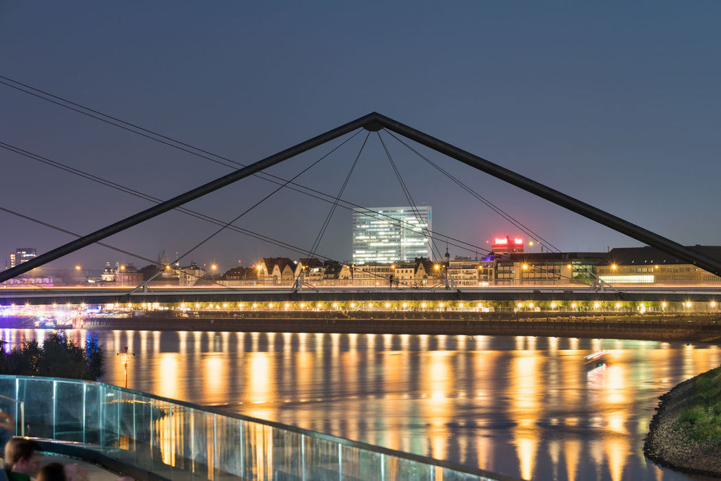 DUESSELDORF, GERMANY - SEPTEMBER 14, 2016: The new media harbor provides a spectecular view on the Rhine promenade during sunset. Architecture Attraction Bridge - Man Made Structure Built Structure City Düsseldorf Germany Illuminated M Medienhafen New Media Harbor Night People Place To Be  Reflection River Scenics Ship Sky Tourism Transportation Travel Destinations Urban Urban Geometry Water