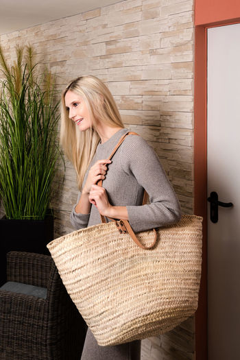 Young woman carrying straw bag while standing in waiting room