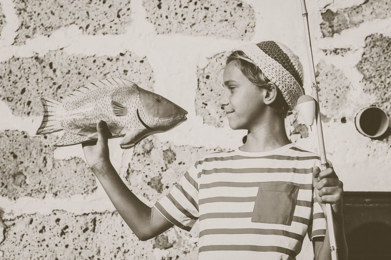 Smiling boy holding toy fish and rod against stone wall