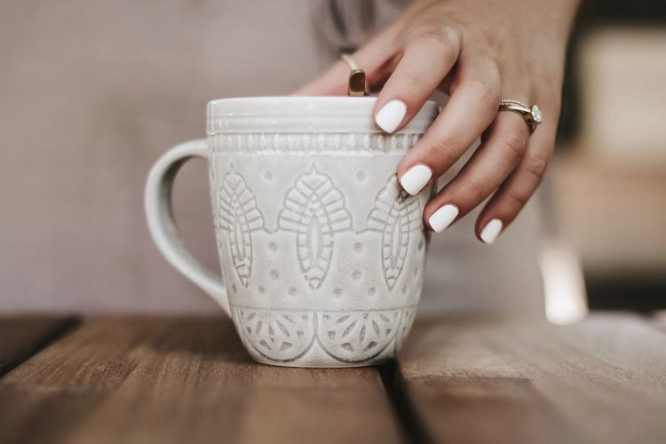 Close-up of woman holding coffee cup on table