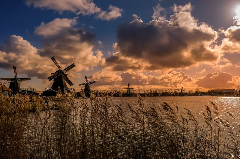 Panoramic view of traditional windmill on field against sky at sunset