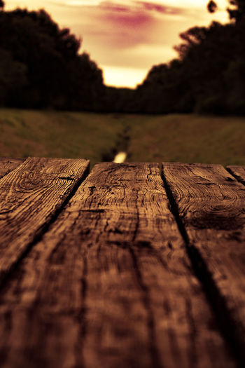 Surface level of wooden railing at sunset