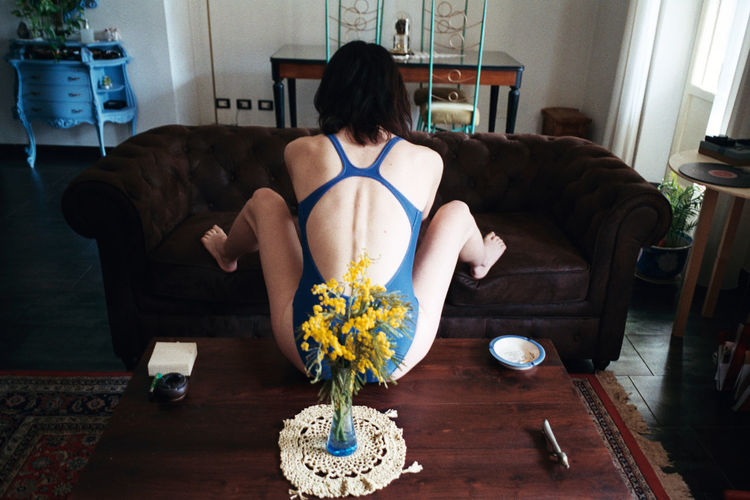 Rear view of woman sitting on sofa at home