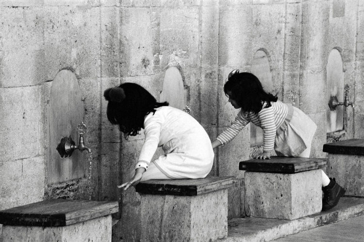 Side view of sisters washing hands