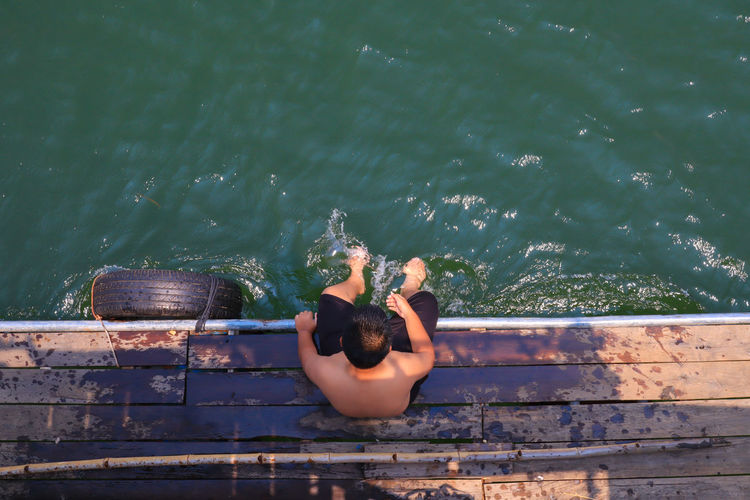 High angle view of shirtless boy sitting on boat deck over lake