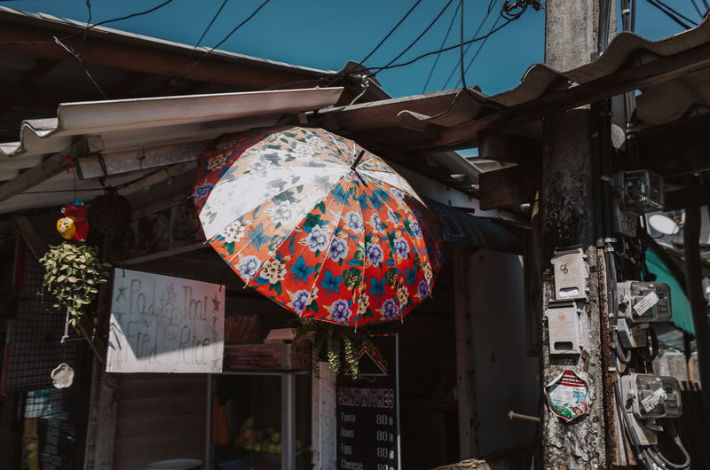 Umbrella protecting a store from the sun in Koh Tao, Thailand Hanging Architecture Built Structure Retail  Market Day No People For Sale Building Exterior Outdoors Market Stall Small Business Business Multi Colored Lighting Equipment Umbrella Retail Display Lantern Roof Pattern Floral Pattern Colorful Color Heat - Temperature Hot ASIA Messy Thailand Koh Tao