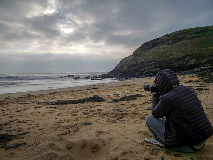 she loves watching Autumn Winter Photographing The Photographer Photographing Nature Woman Sat On The Sand Cross Legged Taking Photkgraphs Sea Beach Water Sand Women Sky Horizon Over Water Cloud - Sky Overcast Rock Formation Dramatic Sky Physical Geography Atmospheric Mood 2018 In One Photograph