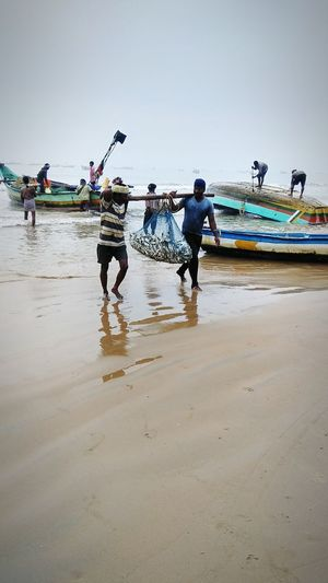 Work even in difficult climatic workers Water Group Of People Land Beach Sea Men Fishing Transportation Teamwork Nature Environment Working Summer Exploratorium Sky Sunset Land Occupation Nautical Vessel People Adult Cooperation Activity Outdoors