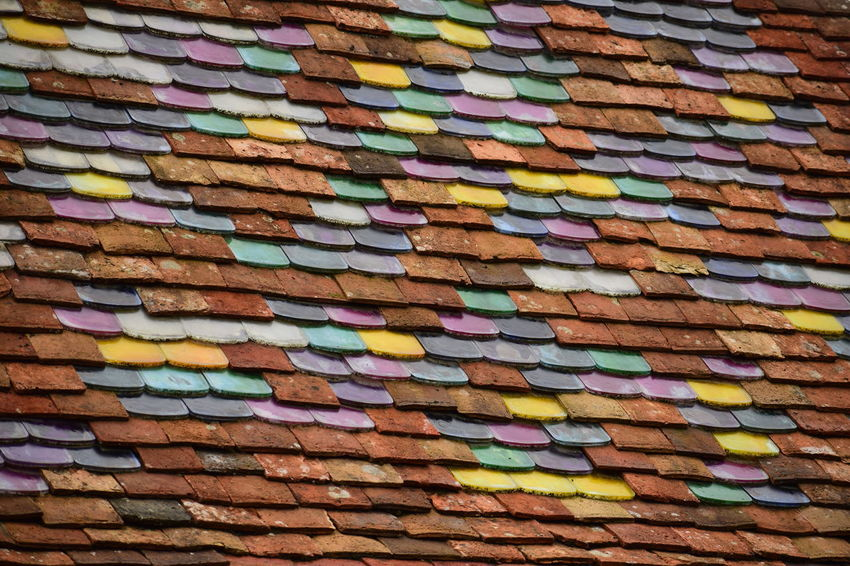 multi colored tiles on a roof Abundance Architecture Arrangement Backgrounds Brick Brick Wall Built Structure Close-up Day Full Frame High Angle View Large Group Of Objects Multi Colored No People Outdoors Pattern Repetition Roof Tile Textured  Wall Wall - Building Feature