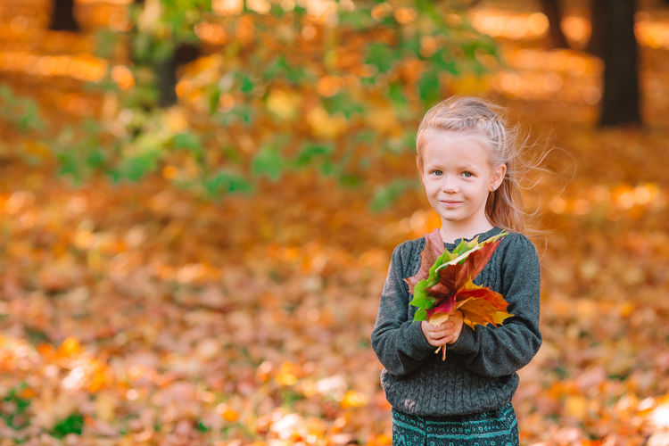 Portrait of smiling girl with autumn leaves