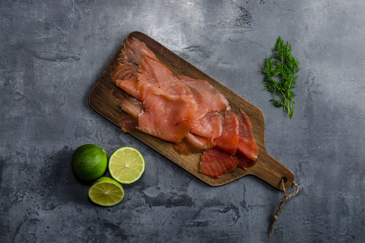 Organic smoked salmon from sustainable fishing farm Salmon - Seafood Salmon Sashimi Smoked Salmon  Healthy Eating Healthy Lifestyle Omega Healthy Fats Diet Sustainable Resources Sustainability Sustainable Lifestyle Norwegian Salmon Scottish Salmon Raw Food Food Fillet Lime Dill Gourmet Food Natural Fish Fishing Food And Drink Freshness No People Meat Indoors  Wellbeing Fruit Lemon Citrus Fruit SLICE Studio Shot Seafood Gray Vegetable Directly Above Gray Background Herb Table Knife