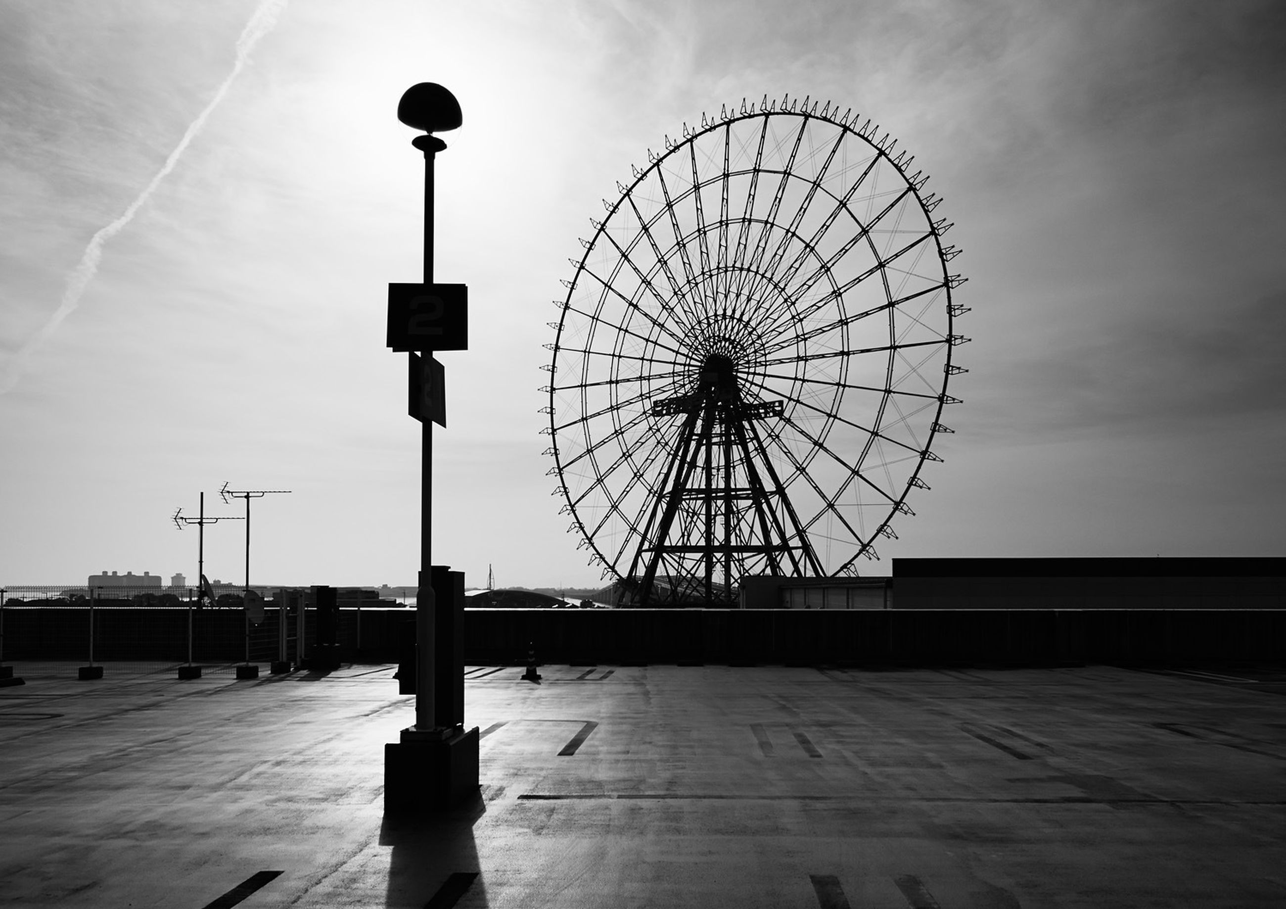 sky, ferris wheel, low angle view, amusement park, amusement park ride, arts culture and entertainment, cloud - sky, silhouette, built structure, street light, outdoors, leisure activity, architecture, cloud, incidental people, bicycle, day, street, road