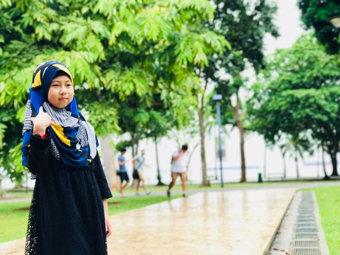 Girl wearing hijab while standing at park