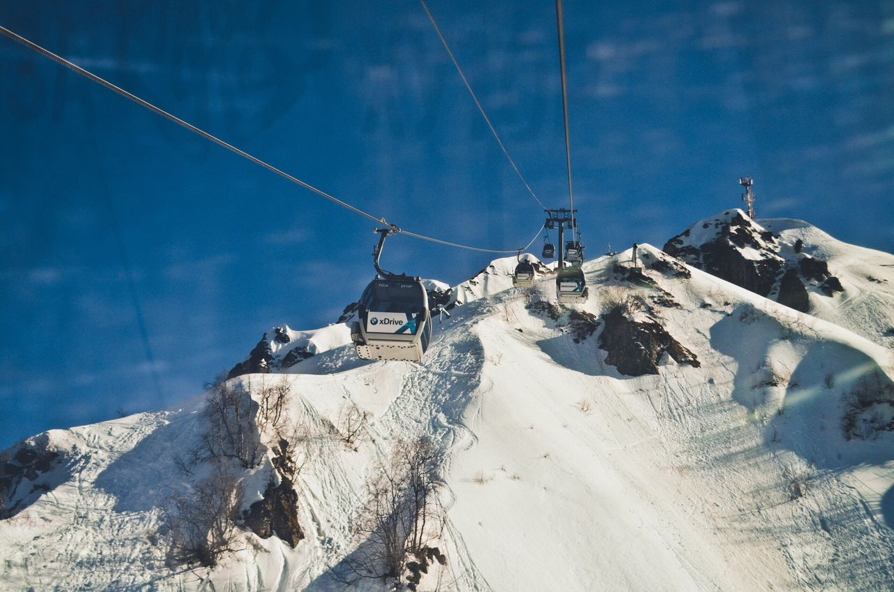 cold temperature, snow, winter, nature, mountain, outdoors, weather, day, sky, cable, transportation, snowcapped mountain, no people, sunlight, scenics, beauty in nature, mode of transport, tranquility, mountain range, tranquil scene, ski lift, low angle view, landscape, blue, nautical vessel