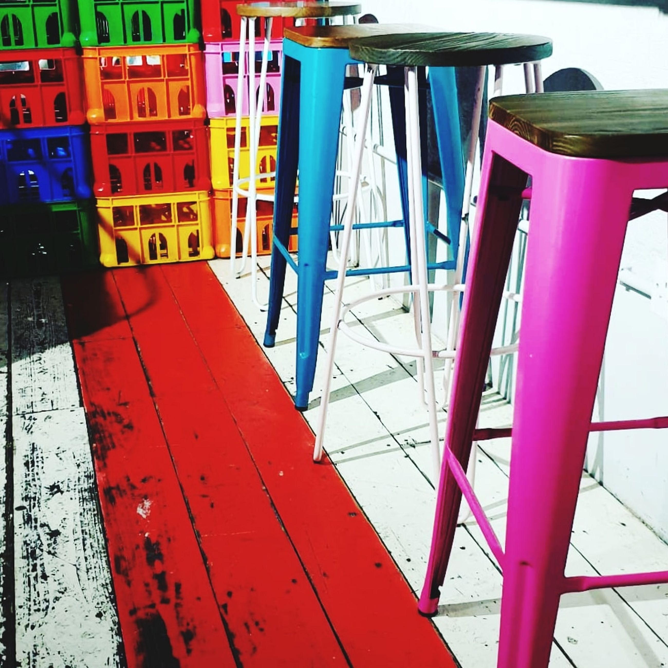 red, no people, seat, day, absence, empty, chair, table, multi colored, indoors, wood - material, business, focus on foreground, flooring, metal, pink color, mode of transportation, nature, arrangement