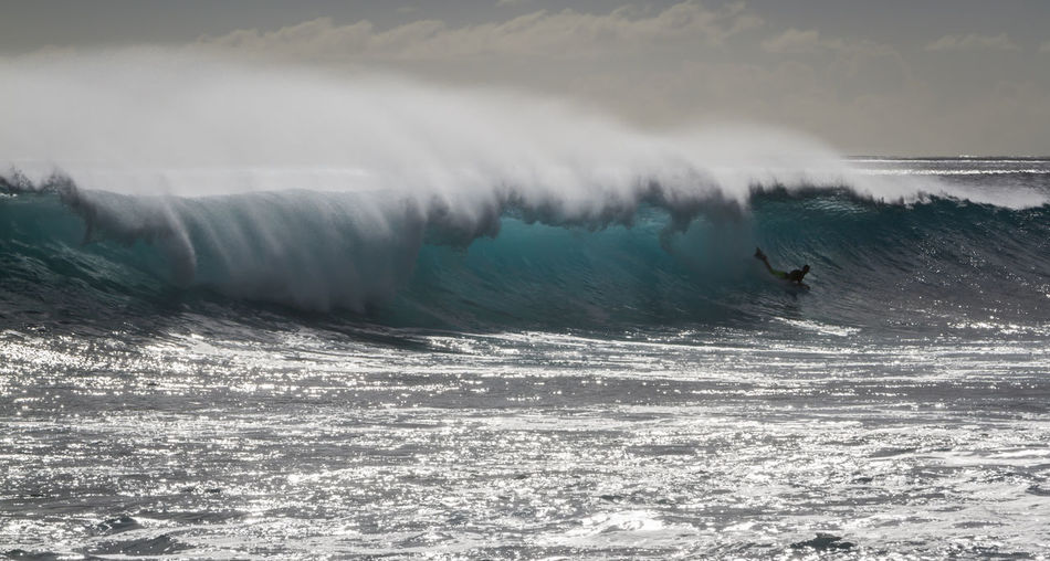 A Man riding a wave Oahu Hawaii Silhouette Adventure Aquatic Sport Back Lit Beauty In Nature Body Boarding Evening Flowing Water Leisure Activity Lifestyles Motion Nature Ocean Outdoors People Power Power In Nature Sea Skill  Sport Surfing Water Waterfront Wave