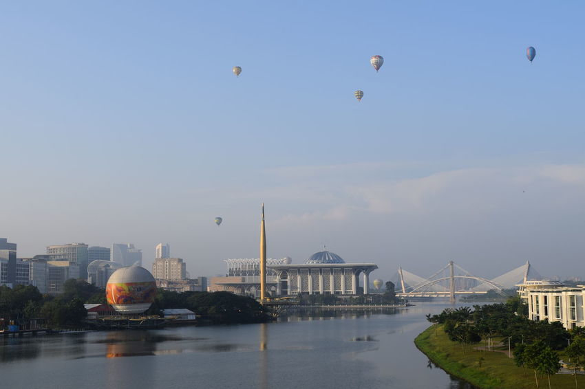 Hot air balloon in Putrajaya, Malaysia. Flying City Travel Destinations Water Urban Skyline Outdoors Sky Motion Cityscape Skyline Morning Light Hot Air Balloon Fiesta Reflection Architecture Flying High