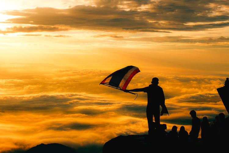 Silhouette man holding thai flag by people on cliff against cloudy sky at sunset