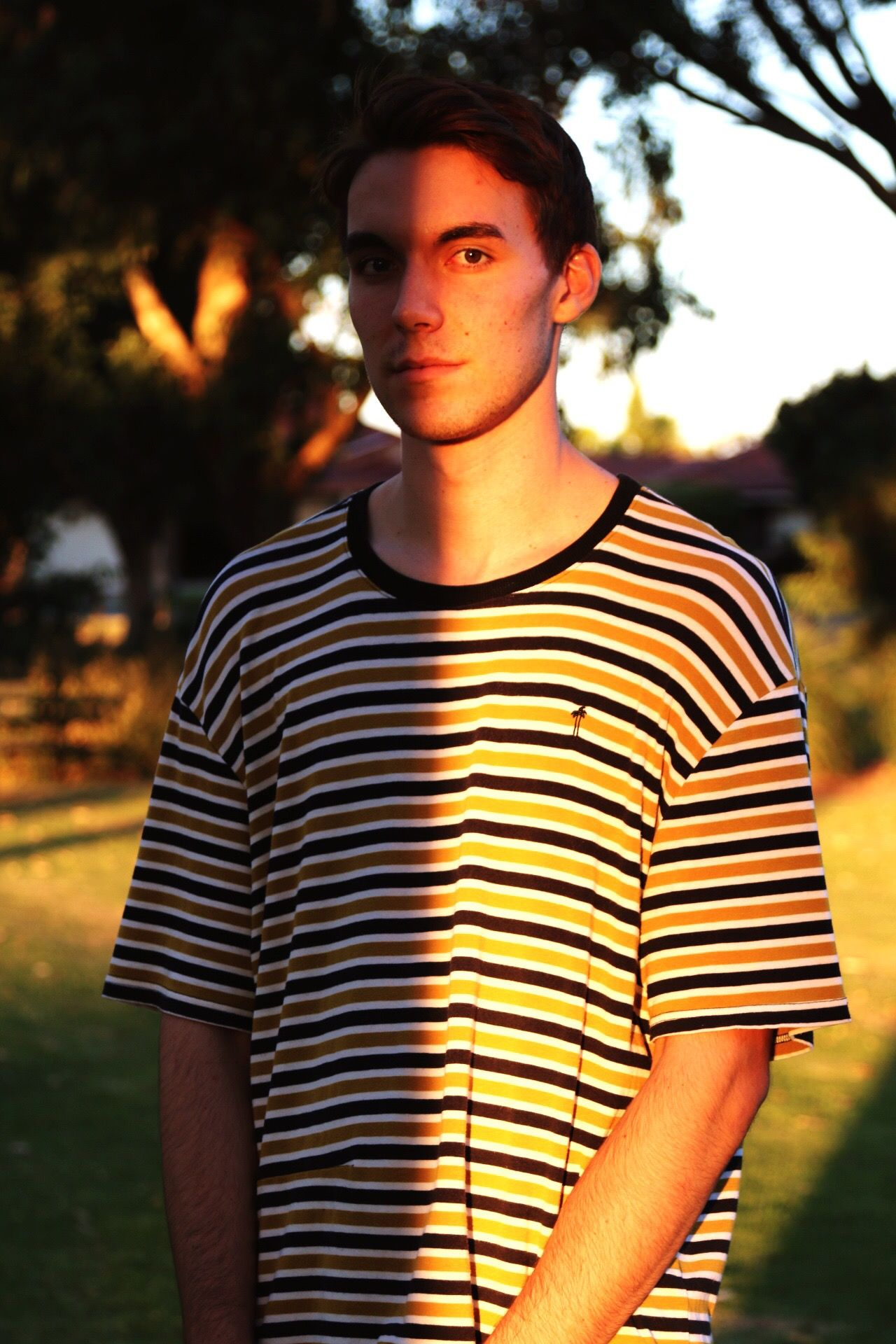 Portrait of young man standing in sunlight at park